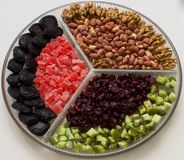Composition with dried fruits and assorted nuts on a glass plate royalty free stock photos
