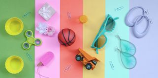 Composition with earrings, sunglasses, beverage can, basketball ball, toy truck, gift box, ice cream, flower and spinner. Trendy pastel composition with earrings royalty free stock image