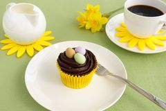 Composition with Easter Cupcake and Coffee. Composition with Easter chocolate cupcake decorated with Easter eggs, a cup of coffee, milk jar and narcissus flowers Royalty Free Stock Photos