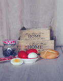 Composition with Easter eggs, bread, wooden baskets and chocolate candies in a jar. Royalty Free Stock Photos