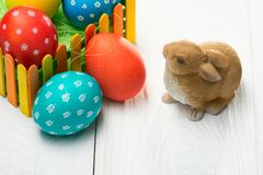 Composition with Easter eggs on the fence and the rabbit on wooden background. F stock photo