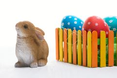 Composition with Easter eggs on the fence and the rabbit on wooden background. F stock photos