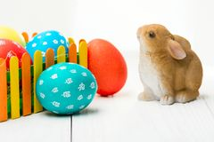 Composition with Easter eggs on the fence and the rabbit on wooden background. F stock image