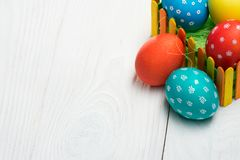 Composition of eggs for Easter behind a colorful fence on a wooden table. G royalty free stock images
