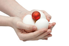 Composition from eggs and a New Year's sphere. In hands isolated on white with local focus Royalty Free Stock Photos