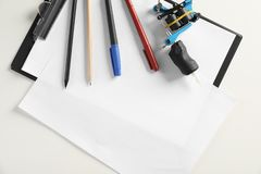 Composition with empty sheet of paper and tattoo machine on white background, top view. Space for text stock photo