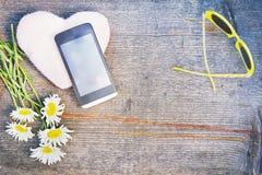 Composition en été avec des fleurs de smartphone et de camomille Photo libre de droits