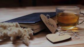 Composition en amour sur une table en bois Le livre, épillets d'une usine d'or, une tasse de thé, coeurs sur une table en bois banque de vidéos