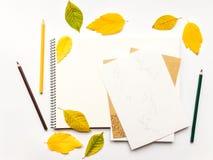 Composition en automne avec l'album et les crayons, décorés des feuilles de jaune et de vert Configuration plate, vue supérieure Photographie stock