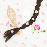 Composition en beauté avec le peigne en bois pour dénommer de cheveux, shampooing et fleurs roses sur le fond blanc Configuration Photographie stock libre de droits