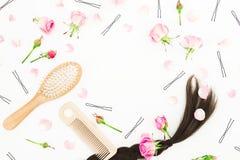 Composition en blog de beauté avec le peigne pour dénommer de cheveux, barrette et fleurs roses sur le fond blanc Configuration p Image stock