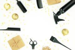 Composition en cadre de coiffeur de Noël avec le jet, les peignes, les ciseaux et le boîte-cadeau avec des boules sur le fond bla image stock