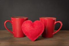 Composition en jour de valentines avec les tasses de café rouges et coeur de feutre au-dessus de conseil en bois avec le chalckbo Photographie stock