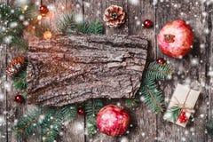 Composition en Noël avec des cadeaux de Noël, texture d'écorce, crayon, branches de sapin, cônes de pin sur le fond en bois image stock