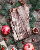 Composition en Noël avec des cadeaux de Noël, texture d'écorce, grenade, branches de sapin sur le fond en bois photos stock
