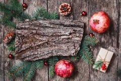 Composition en Noël avec des cadeaux de Noël, texture d'écorce, grenade, branches de sapin sur le fond en bois photographie stock libre de droits