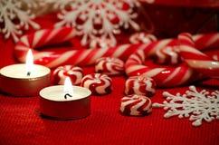 Composition en Noël avec la sucrerie et les bougies rouges et blanches Photographie stock libre de droits