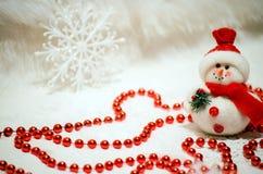 Composition en Noël avec le bonhomme de neige et les perles rouges Photo libre de droits