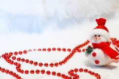 Composition en Noël avec le bonhomme de neige et les perles rouges Photos libres de droits