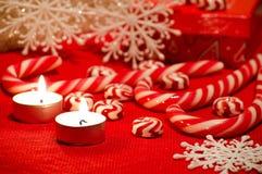 Composition en Noël avec le caramel rouge et blanc bougies et Sn Photographie stock libre de droits