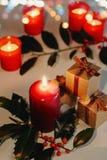Composition en Noël et en nouvelle année Boîtes de bougie de Lit et actuelles et branche de houx images stock