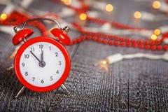 Composition en Noël - réveil rouge sur un boa en bois texturisé Photographie stock