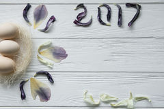 Composition en Pâques avec des oeufs et des pétales violets secs des fleurs Inscription 2017 Photographie stock