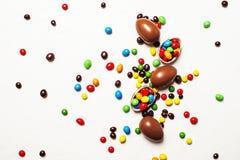 Composition en Pâques avec les oeufs de chocolat et la sucrerie colorée, blancs