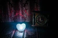Composition en Saint-Valentin avec le bonbon brûlant le coeur multicolore sur le fond foncé et la vieille horloge de vintage, le  Images stock