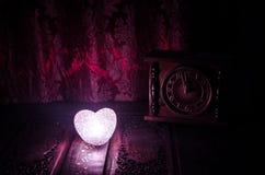 Composition en Saint-Valentin avec le bonbon brûlant le coeur multicolore sur le fond foncé et la vieille horloge de vintage, le  Photographie stock libre de droits