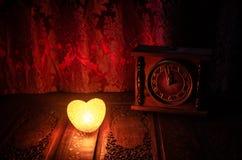 Composition en Saint-Valentin avec le bonbon brûlant le coeur multicolore sur le fond foncé et la vieille horloge de vintage, le  Image libre de droits