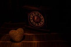 Composition en Saint-Valentin avec le bonbon brûlant le coeur multicolore sur le fond foncé et la vieille horloge de vintage, le  Photos stock
