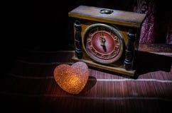 Composition en Saint-Valentin avec le bonbon brûlant le coeur multicolore sur le fond foncé et la vieille horloge de vintage, le  Photo libre de droits