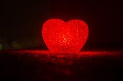 Composition en Saint-Valentin avec le bonbon brûlant le coeur multicolore sur le fond foncé, le centre sélectif, ou la carte de v Images stock