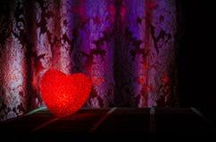 Composition en Saint-Valentin avec le bonbon brûlant le coeur multicolore sur le fond foncé, le centre sélectif, ou la carte de v Photo stock