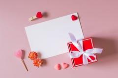 Composition en Saint Valentin : le boîte-cadeau rouge avec l'arc, le calibre de papeterie/photo, les petits coeurs, la sucrerie,  Photo libre de droits