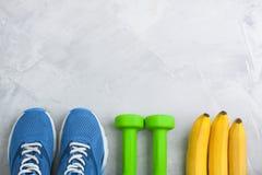 Composition en sport de Flatlay avec des espadrilles, des bananes et la bouteille de W Photographie stock libre de droits
