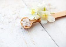 Composition en station thermale avec les fleurs de jasmin et le sel de mer sur la table en bois blanche Images stock