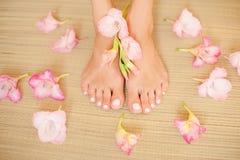 Composition en station thermale - femelle de pied avec clous et fleurs rose-clair sur le tapis de paille Images stock