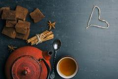 Composition en thé avec la guimauve, la tasse de thé et la théière traditionnelle sur le fond foncé Photographie stock