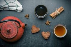 Composition en thé avec la guimauve, la tasse de thé et la théière traditionnelle sur le fond foncé Photographie stock libre de droits