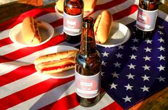 Composition en vacances avec les bouteilles multiples de bière et de hot-dogs, drapeau américain Célébration du Jour de la Déclar Photographie stock