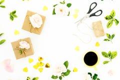 Composition en vue avec des roses, des cadeaux, des ciseaux, la tasse de café et des confettis sur le fond blanc Configuration pl photographie stock