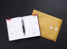 A composition of an envelope and an opened notebook Stock Images