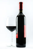 Composition of an exquisite bottle of wine and an elegant glass of red wine on a white background Stock Image