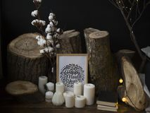 Composition from fellings of trees against a dark background, standing on a wooden floor together with candles and an inscription stock photos