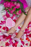 Composition, female feet in sandals on a sheet with rose petals, and a bouquet of roses and a box in the form of a heart with a gi. Ft. Celebration. Birthday stock images