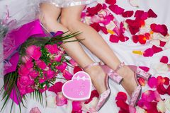 Composition, female feet in sandals on a sheet with rose petals, and a bouquet of roses and a box in the form of a heart with a gi royalty free stock photography