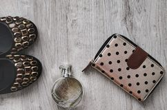 Shoes, perfume, purse. Composition, female shoes with multi-colored large crystals, perfume in a glass bottle and a purse on a wooden background Stock Image
