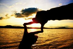 Composition finger frame- man's hands capture sunset at sea. Multicolored horizontal outdoors image. Stock Images